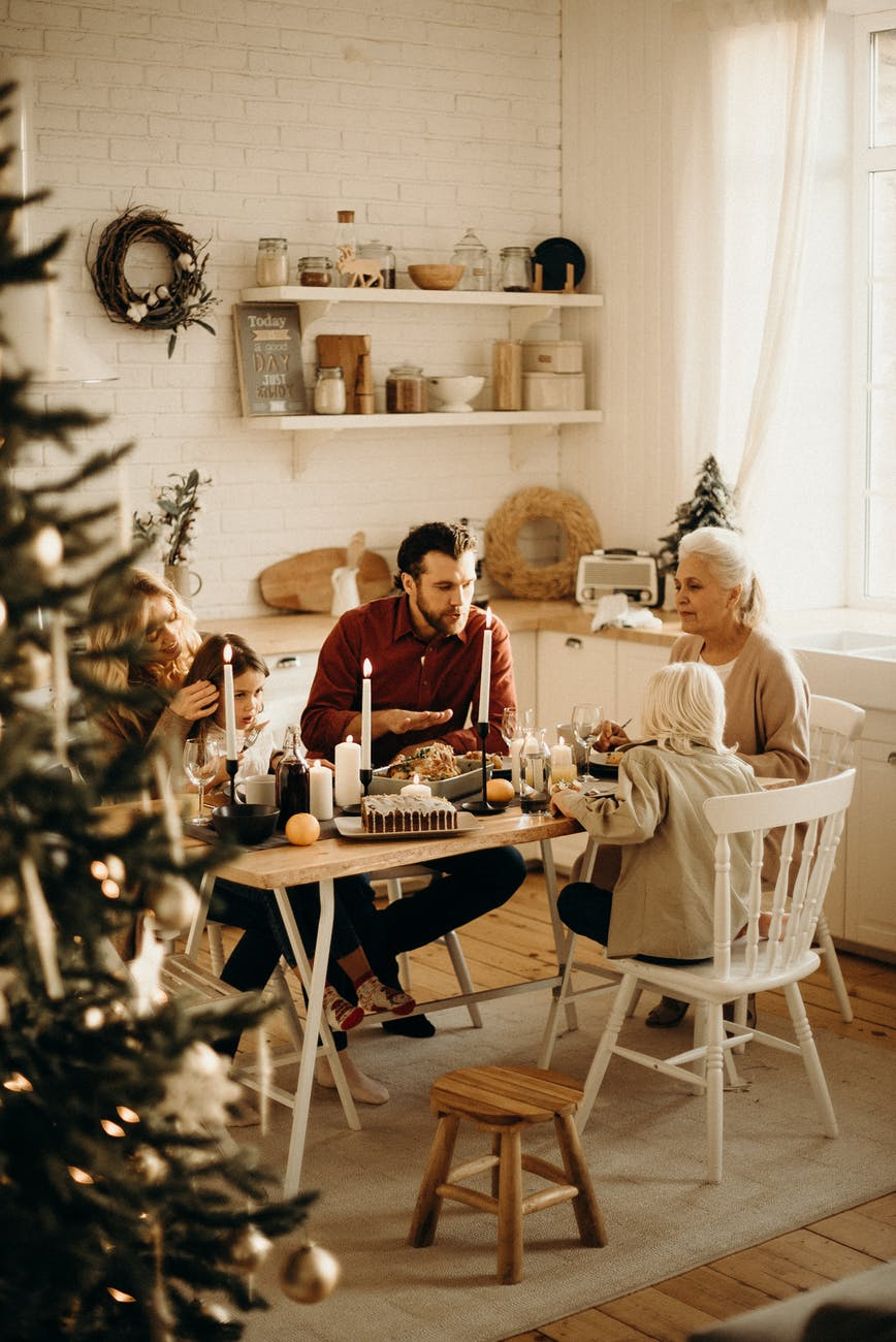 family sitting near dining table and eating food